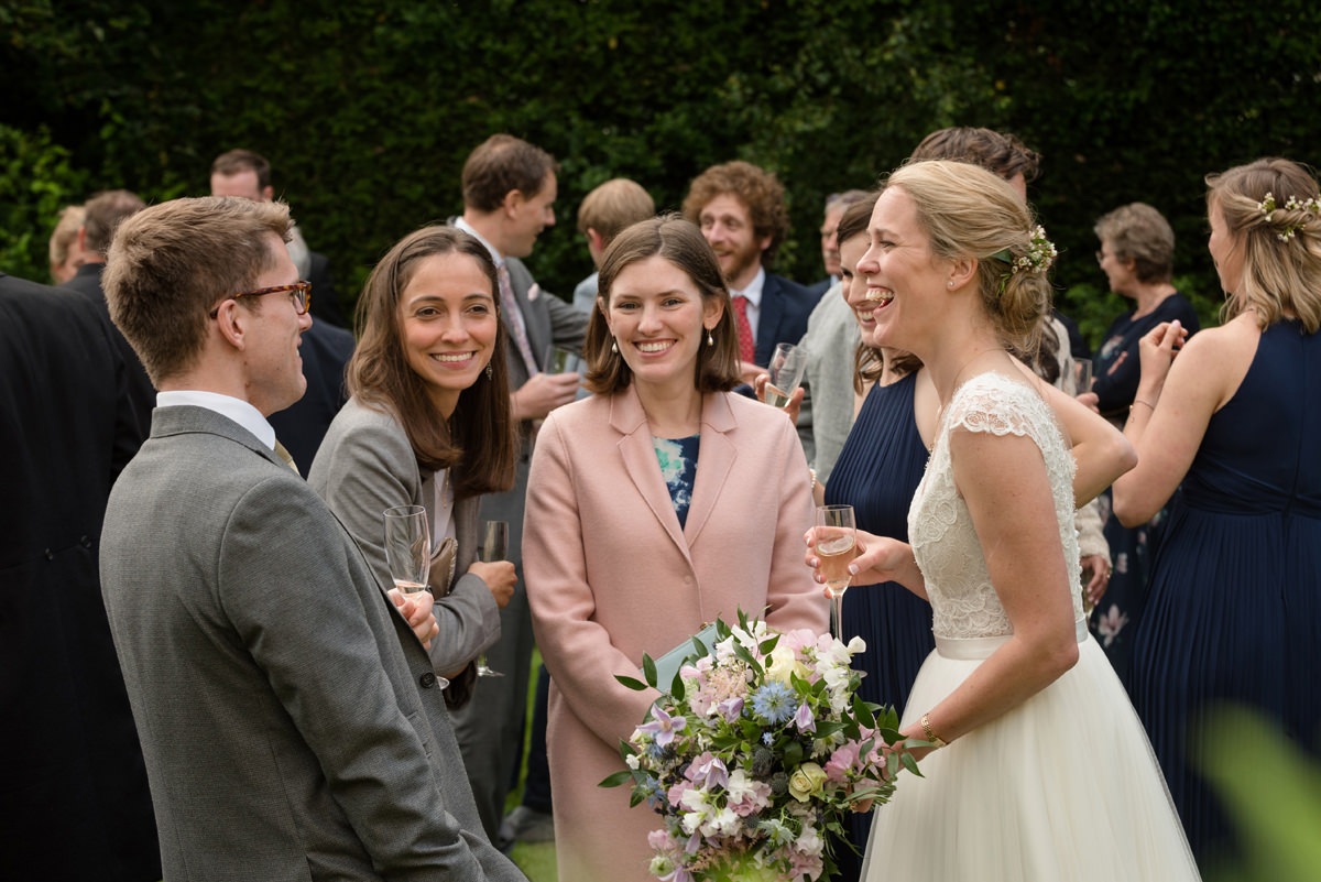 Bride laughing with her friends in Geddington, Northants