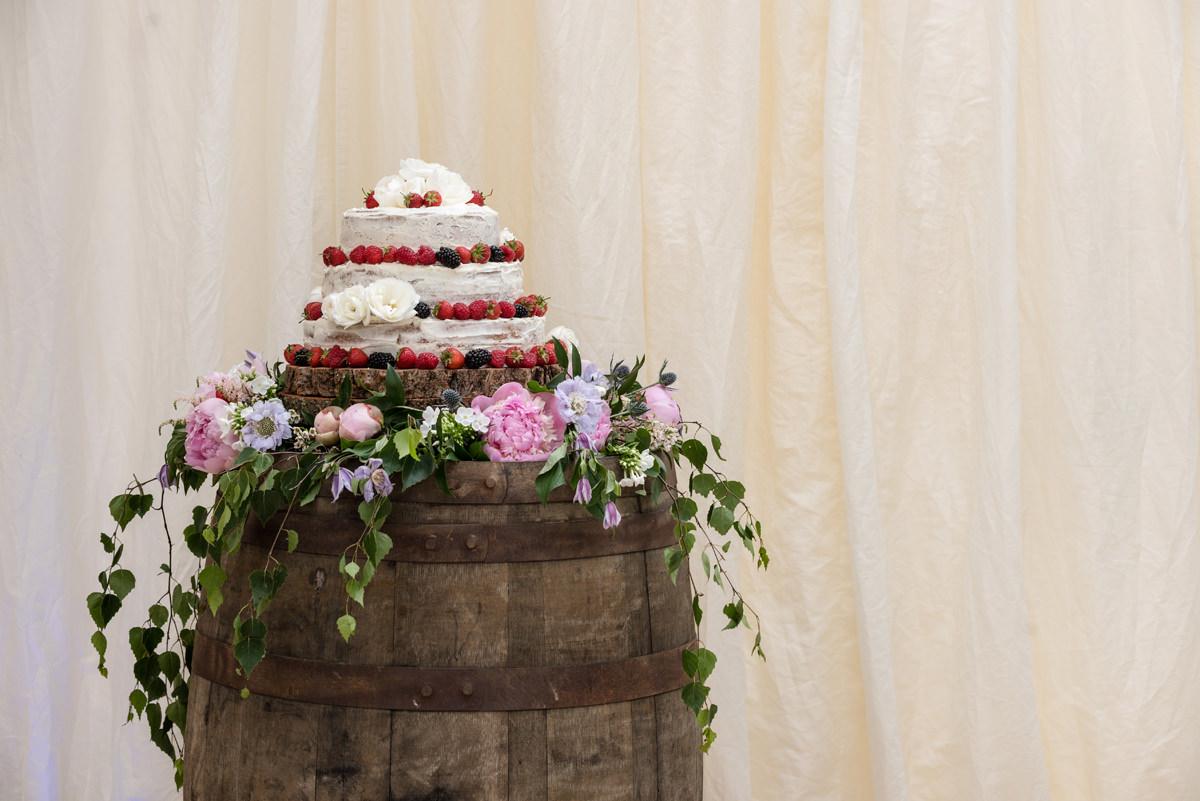 Naked wedding cake on an oak barrel in Geddington, Northants