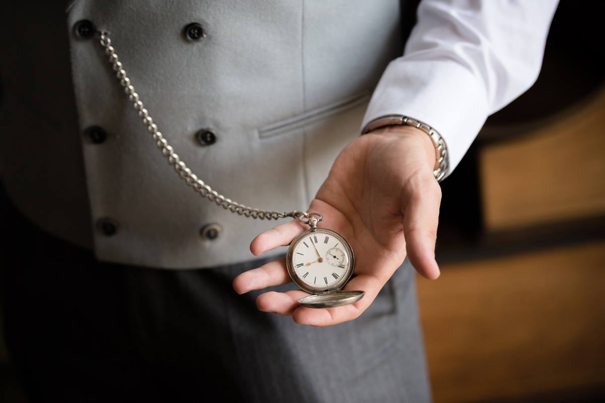 Groom holding his pocket watch in his hand in the Oak Suite at Rushton Hall