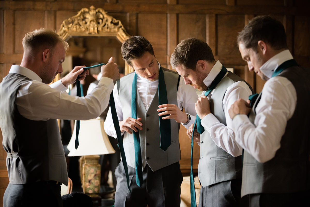 Groomsmen putting their ties on in the Oak Suite at Rushton Hall