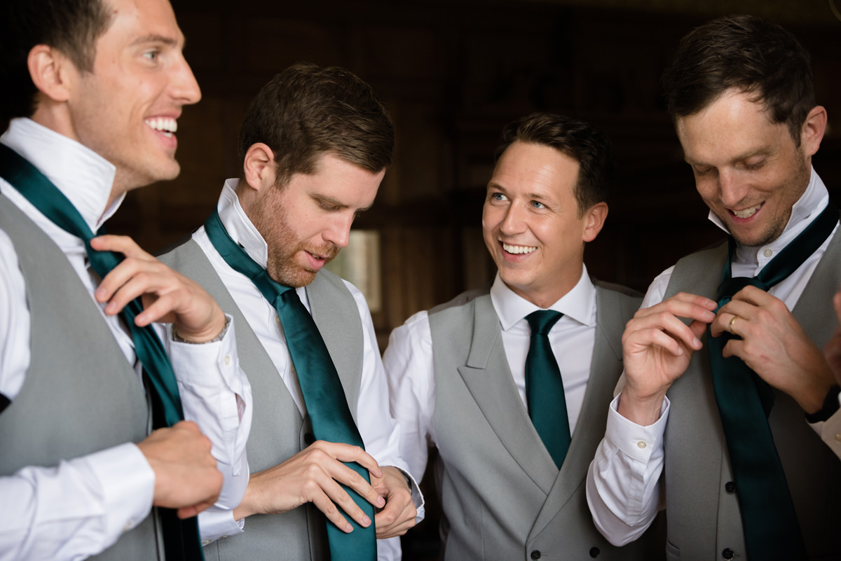 Groom smiling at his ushers doing their ties in the Oak Suite at Rushton Hall
