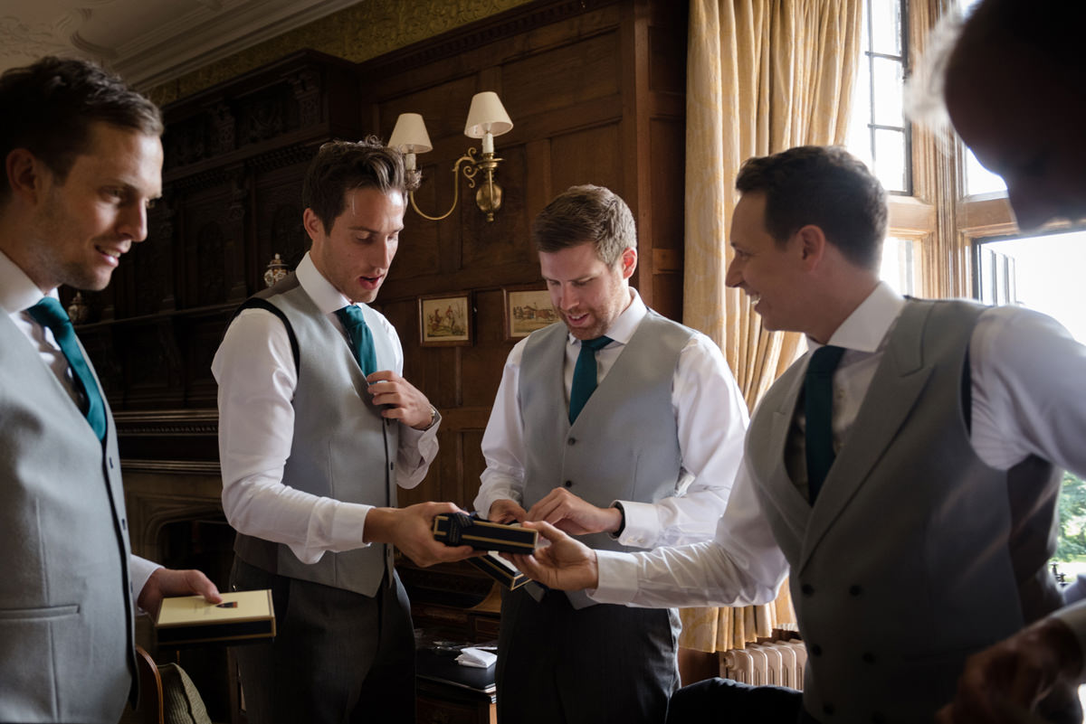 Groom handing out gifts to his ushers in the Oak Suite at Rushton Hall