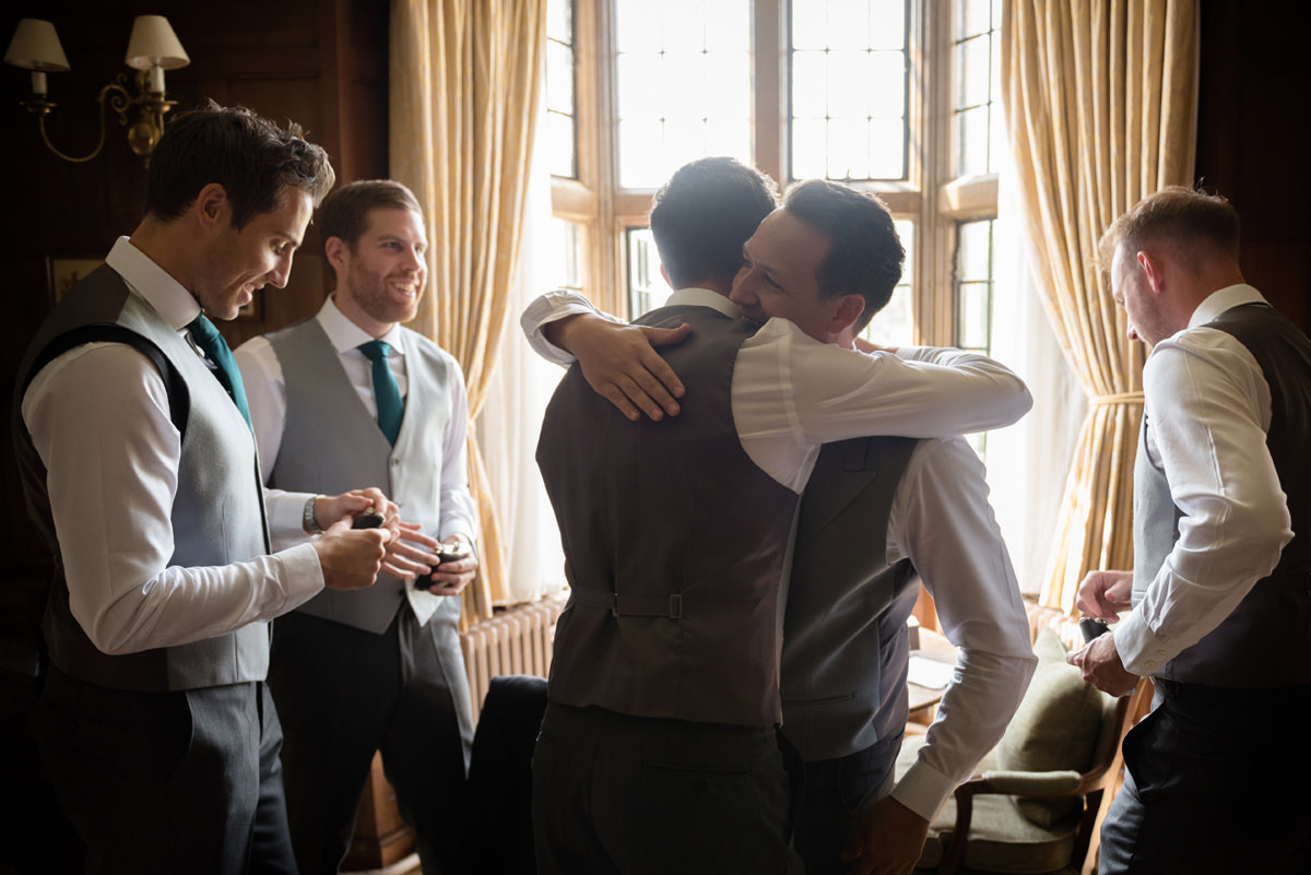 Groom hugging an usher in the Oak Suite at Rushton Hall