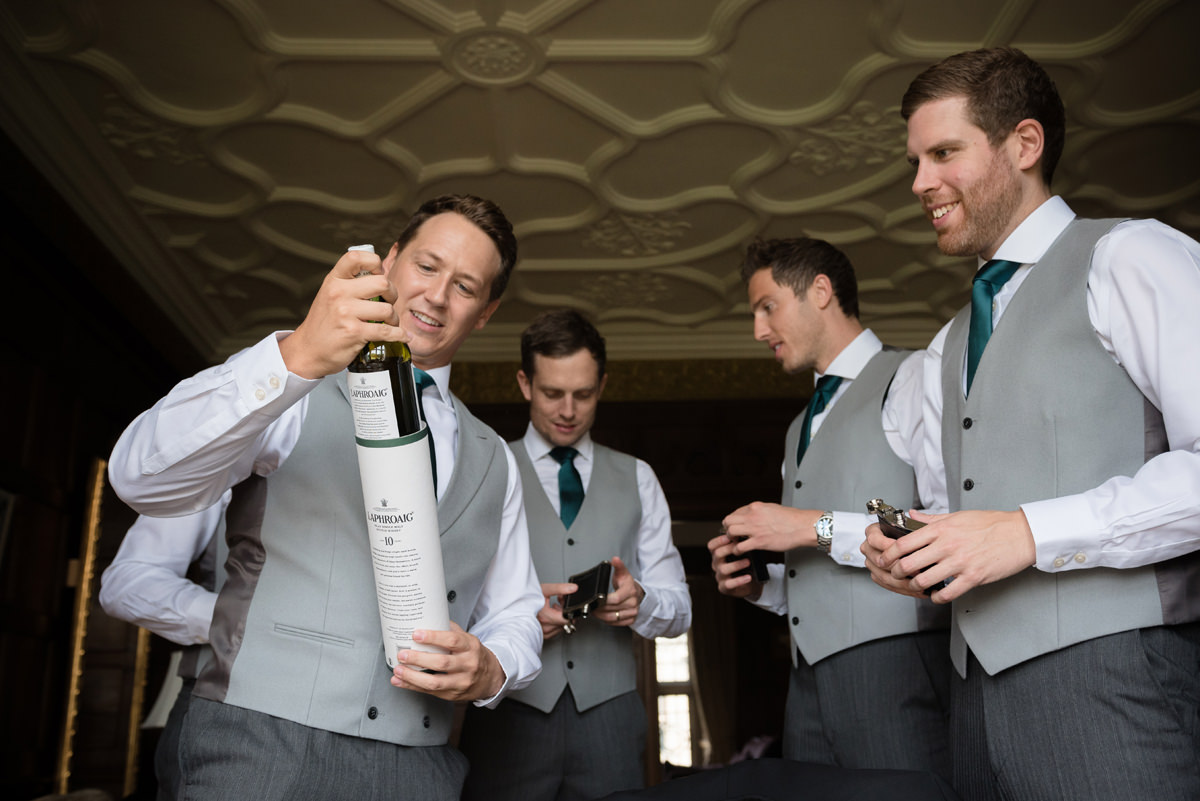 Groom opening a wedding gift from his groomsmen in the Oak Suite at Rushton Hall