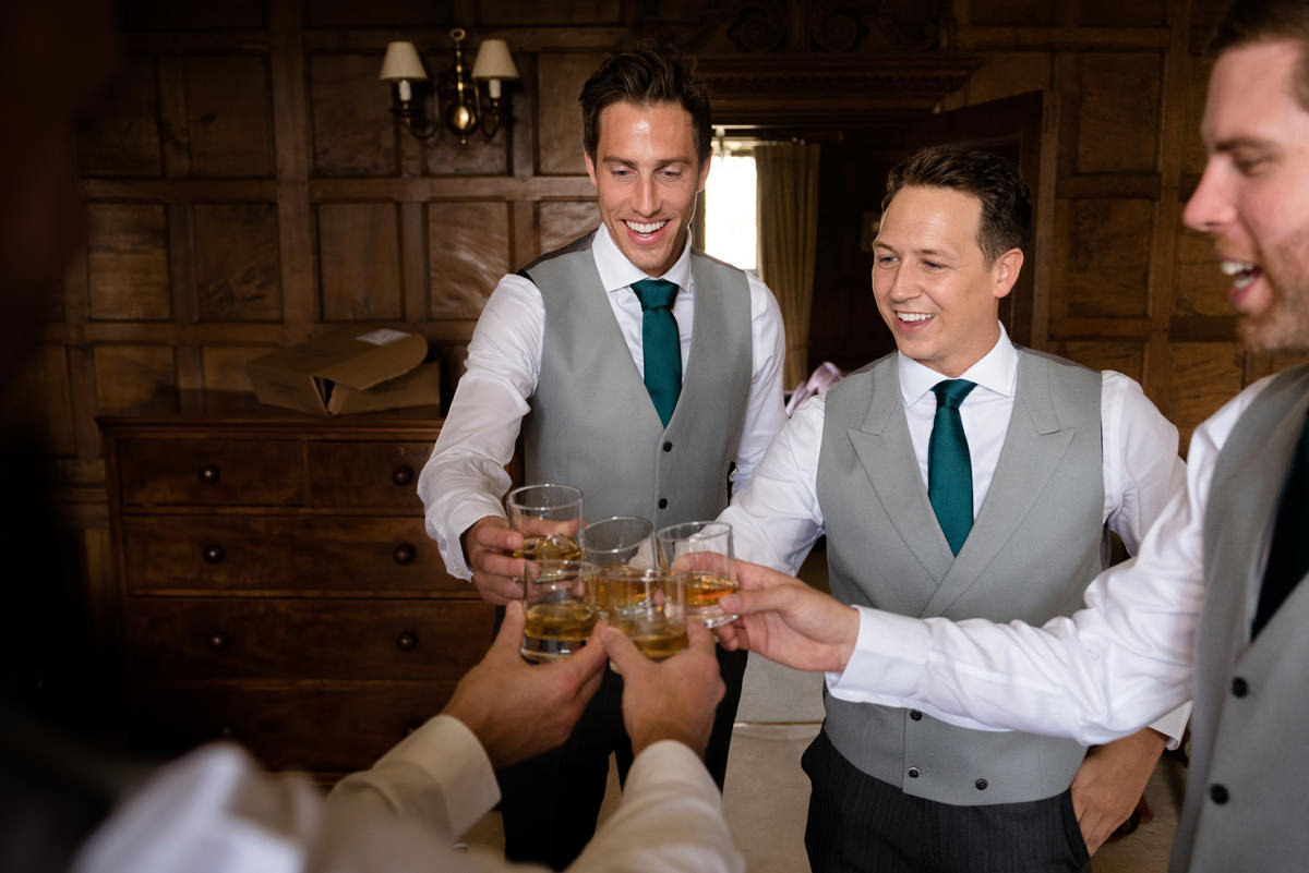 Groomsmen making a toast in the Oak Suite at Rushton Hall