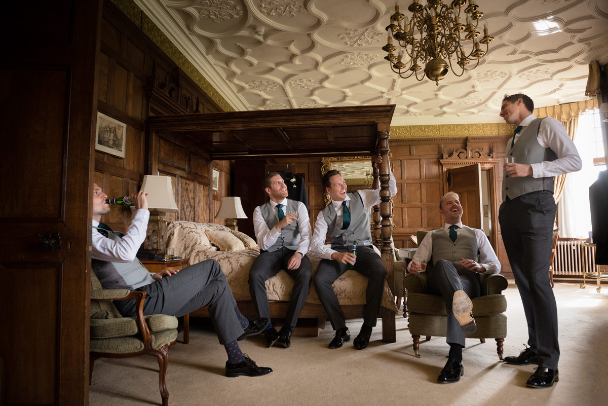 Groomsmen sitting chatting enjoying a drink in the Oak Suite at Rushton Hall