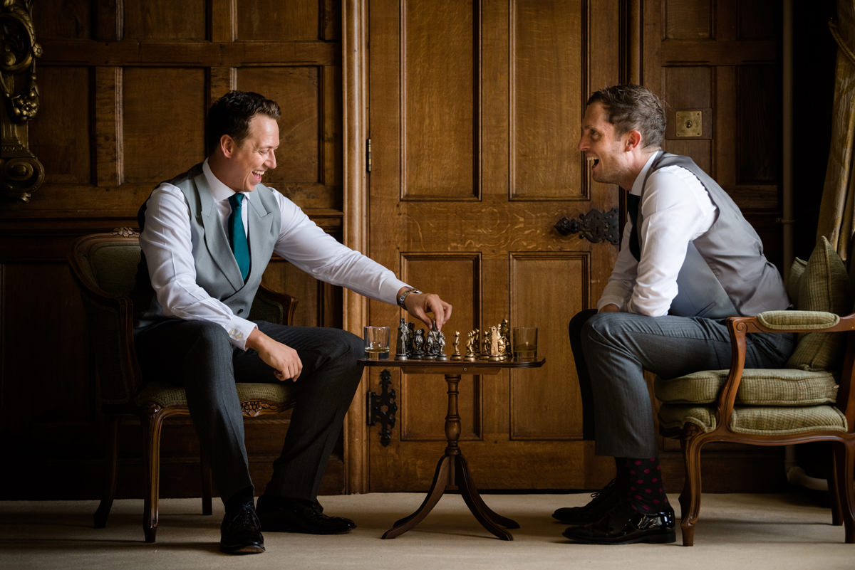 Groomsmen playing chess in the Oak Suite at Rushton Hall