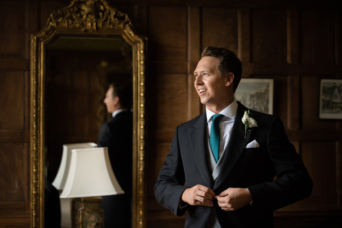 Groom putting his suit jacket on in the Oak Suite at Rushton Hall