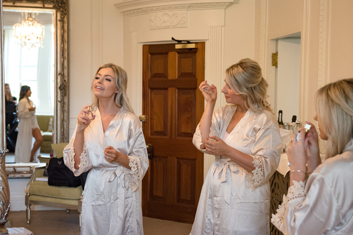 Bridesmaids putting their wedding gift perfume on in The Georgian Suite at Rushton Hall