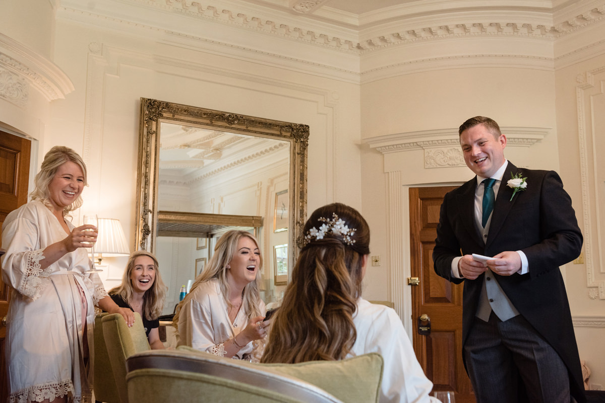Bridesmaids and bridesman laughing in The Georgian Suite at Rushton Hall