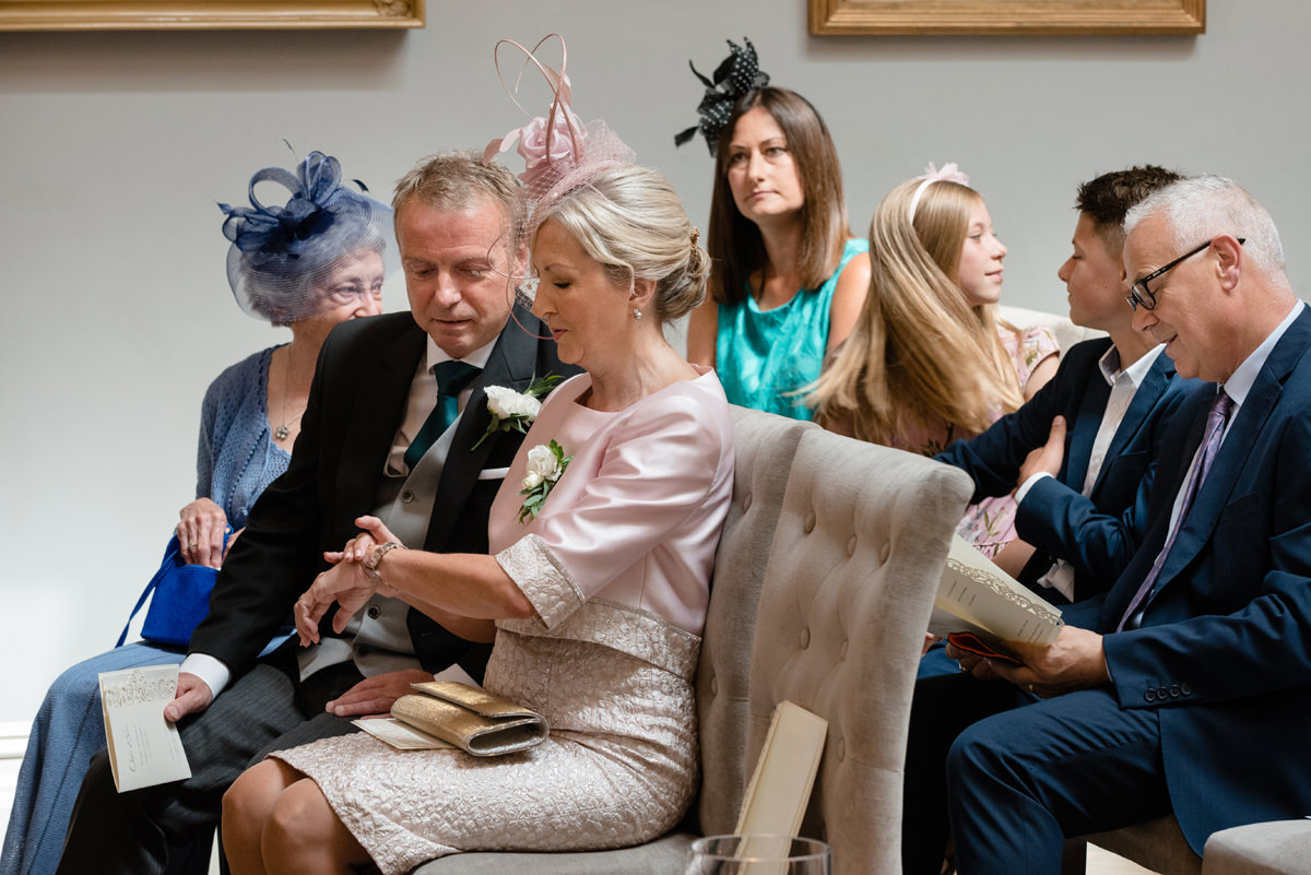 Groom's mum checking the time while waiting for the bride in the Orangery Picture Gallery at Rushton Hall