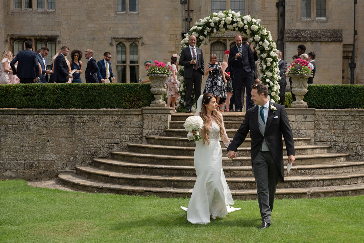 Bride and groom leading guests onto the lawn at Rushton Hall