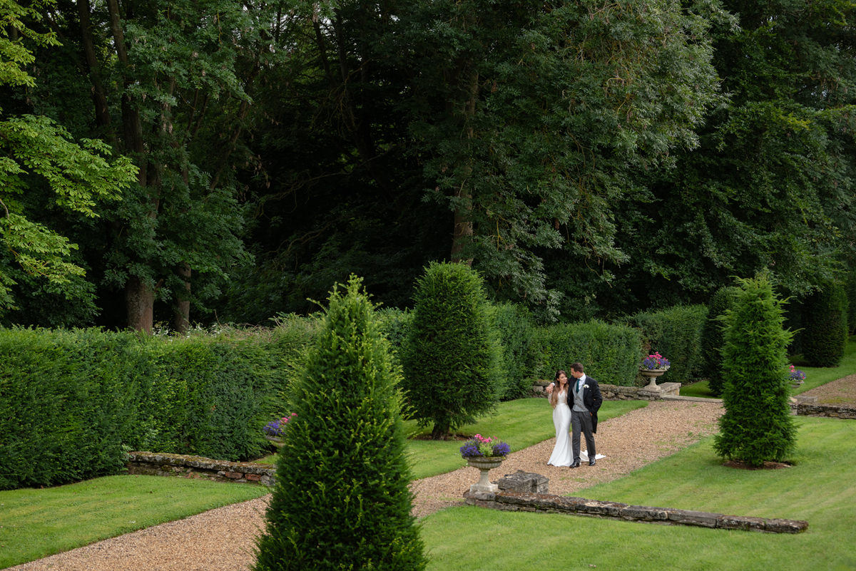 Bride and groom walking in the gardens at Rushton Hall