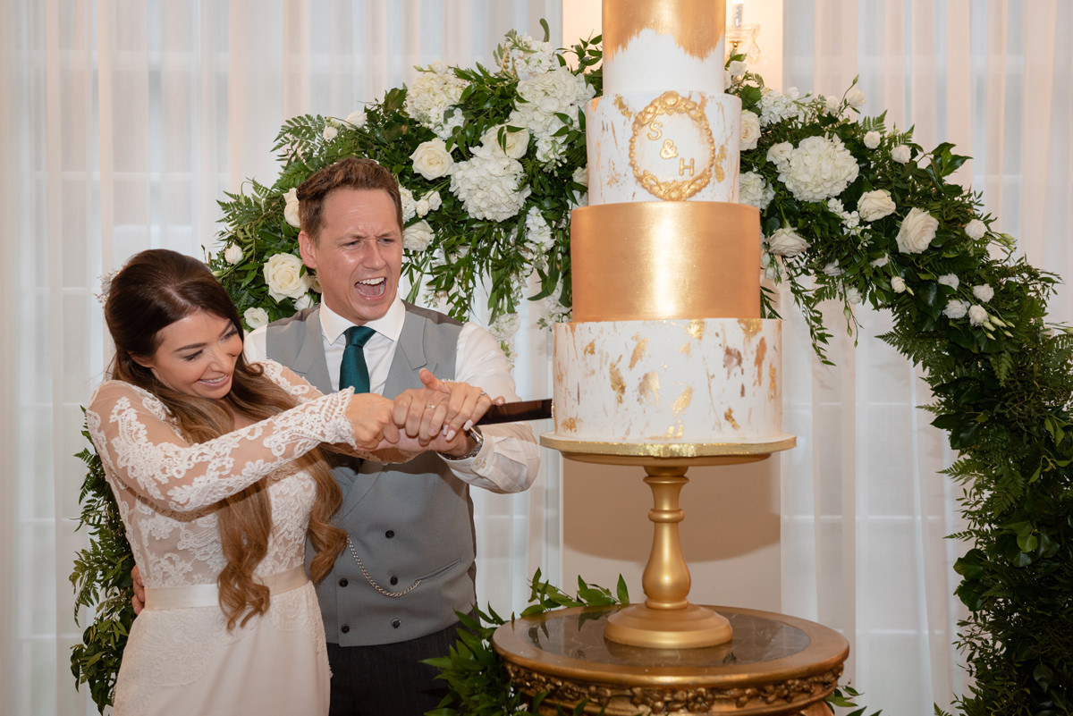Bride and groom cutting a white and gold wedding cake at Rushton Hall