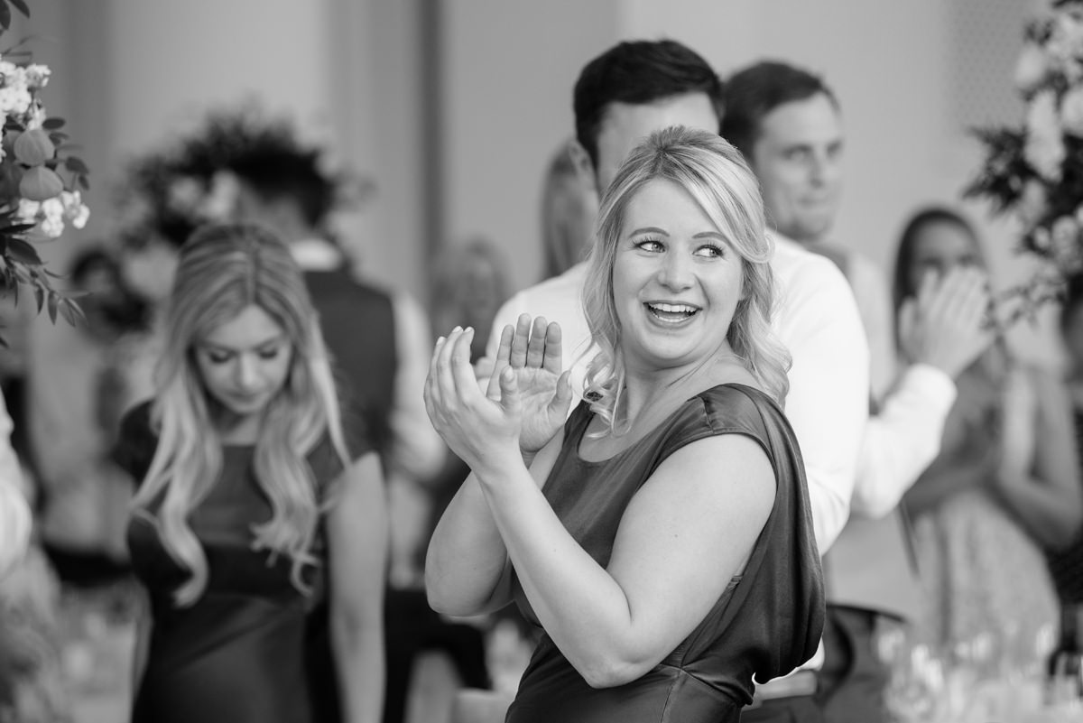 Bridesmaid clapping as couple enter the room for dinner in the orangery at Rushton Hall