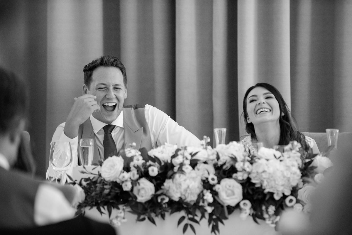 Bride and groom laughing during the best man's speech at Rushton Hall