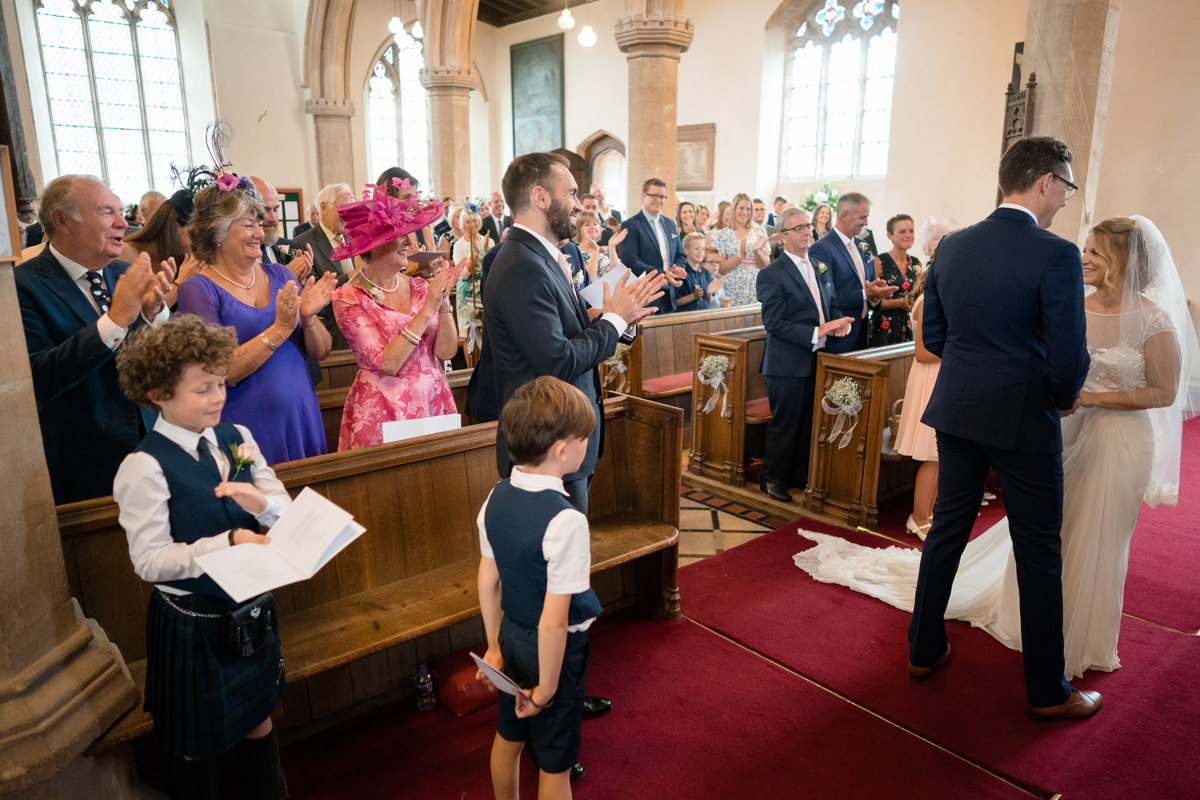 Wedding guests clapping as couple pronounced husband and wife