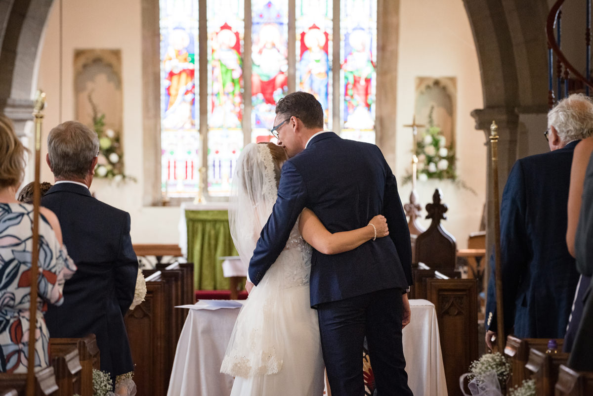 Bride and groom hugging after getting married at Kings Cliffe church