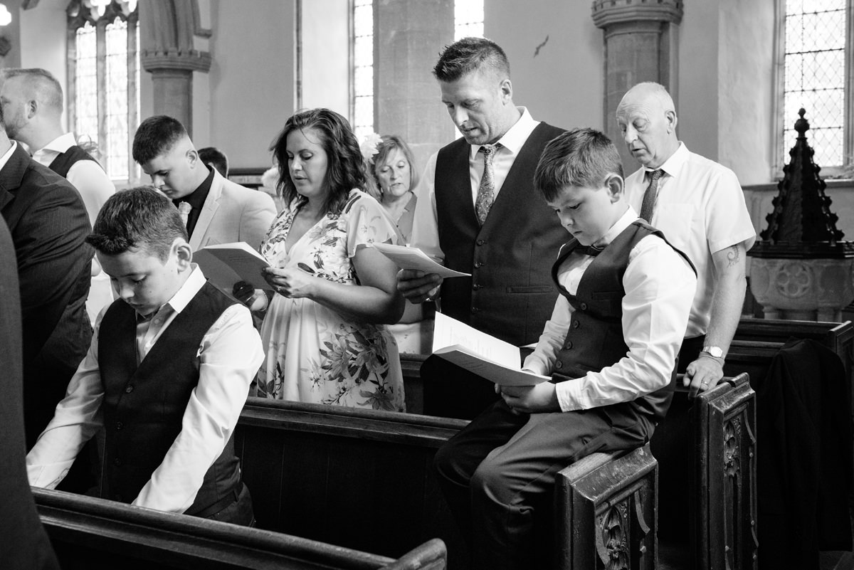 Young wedding guest sitting on back of pew at Kings Cliffe church