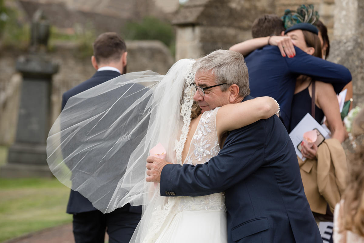 bride and her dad hugging as they come of church