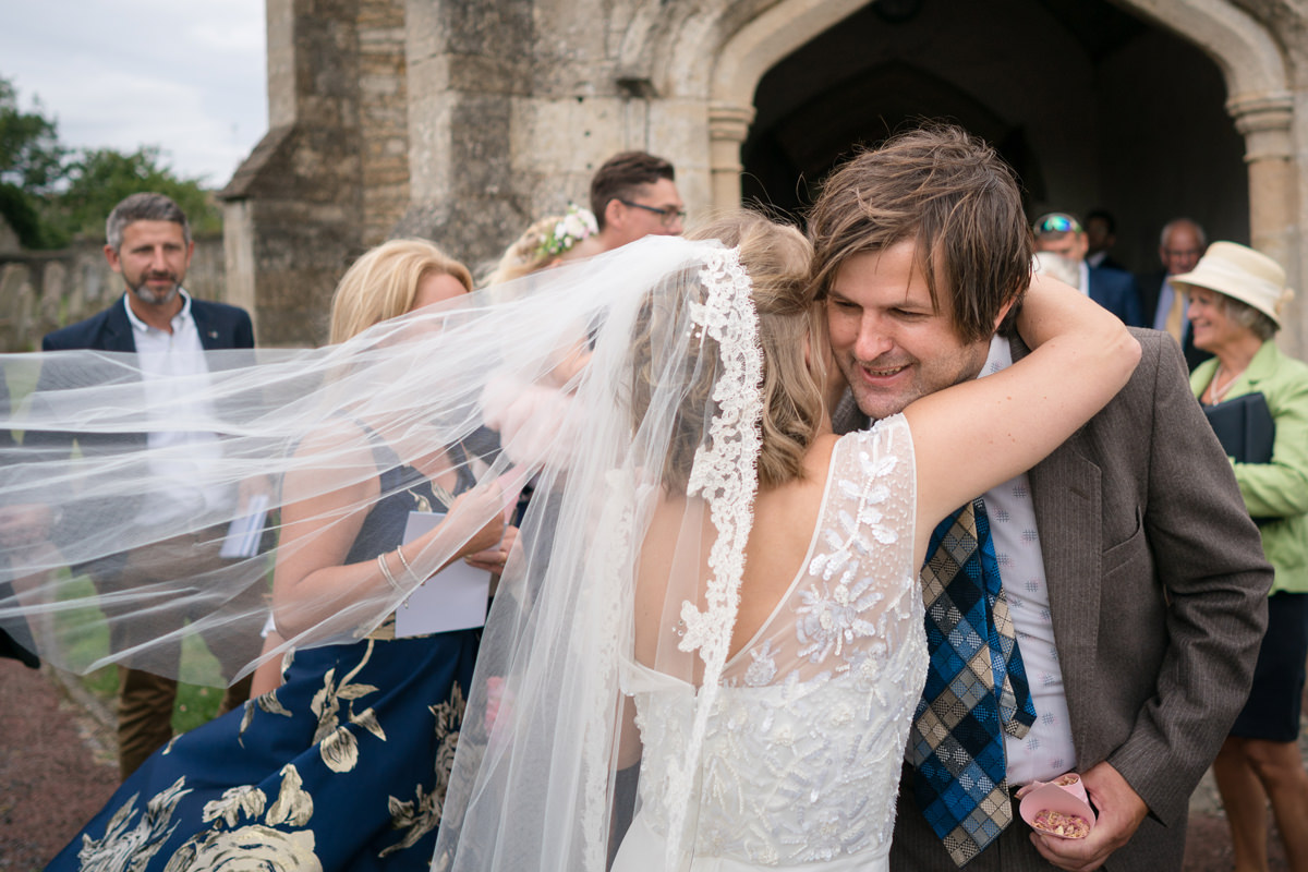 Bride hugging wedding guest coming out of church