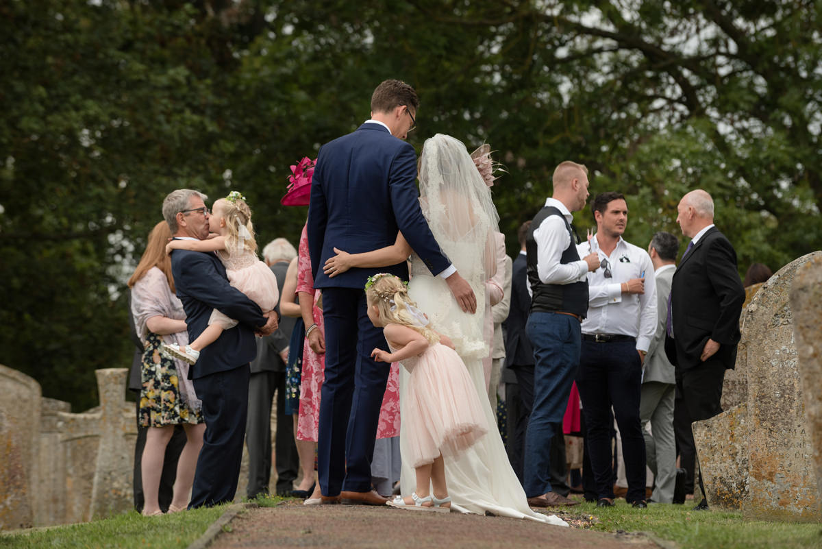 Bride and groom's daughter playing hide & seek behind them