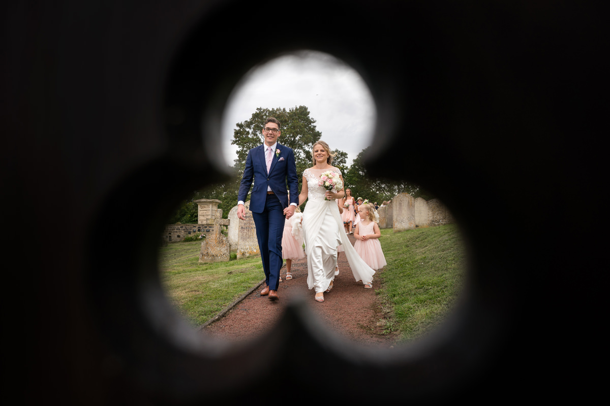 Bride & groom framed by trefoil in church gate
