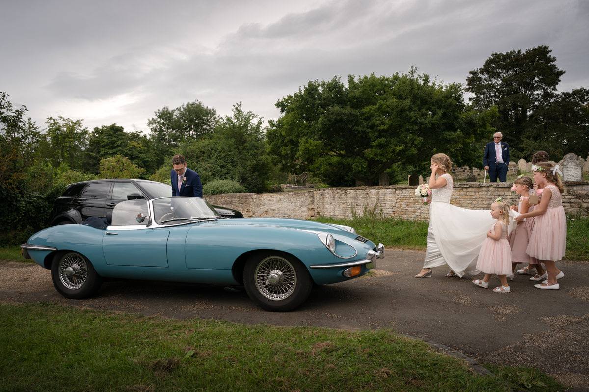 Bride and groom getting into wedding car in Kings Cliffe