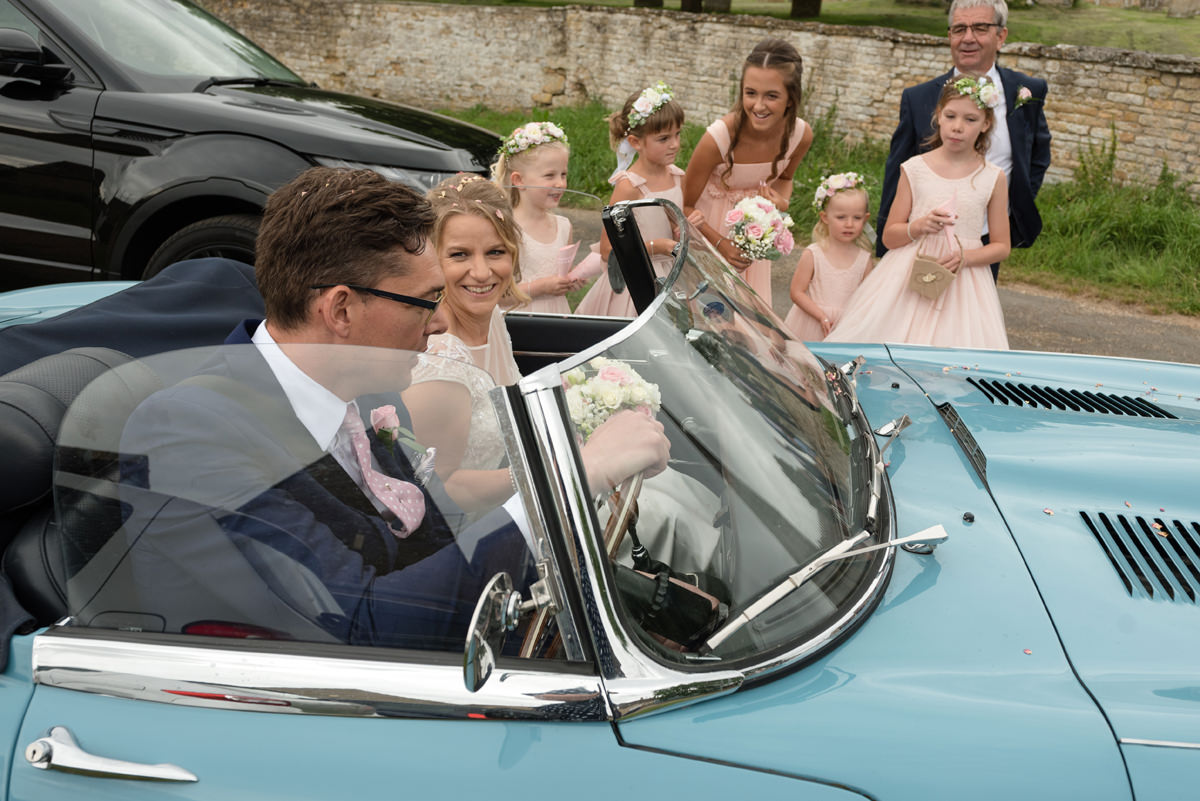 Bride laughing at wedding car not starting