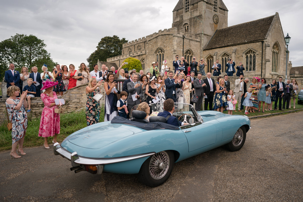 Guests cheering as wedding car leaves Kings Cliffe church