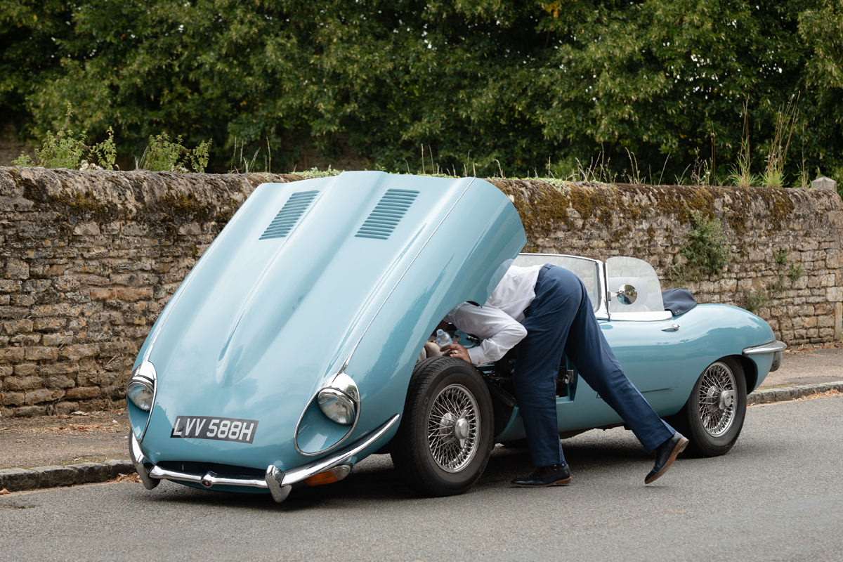 Wedding guest checking under the bonnet of vintage E type