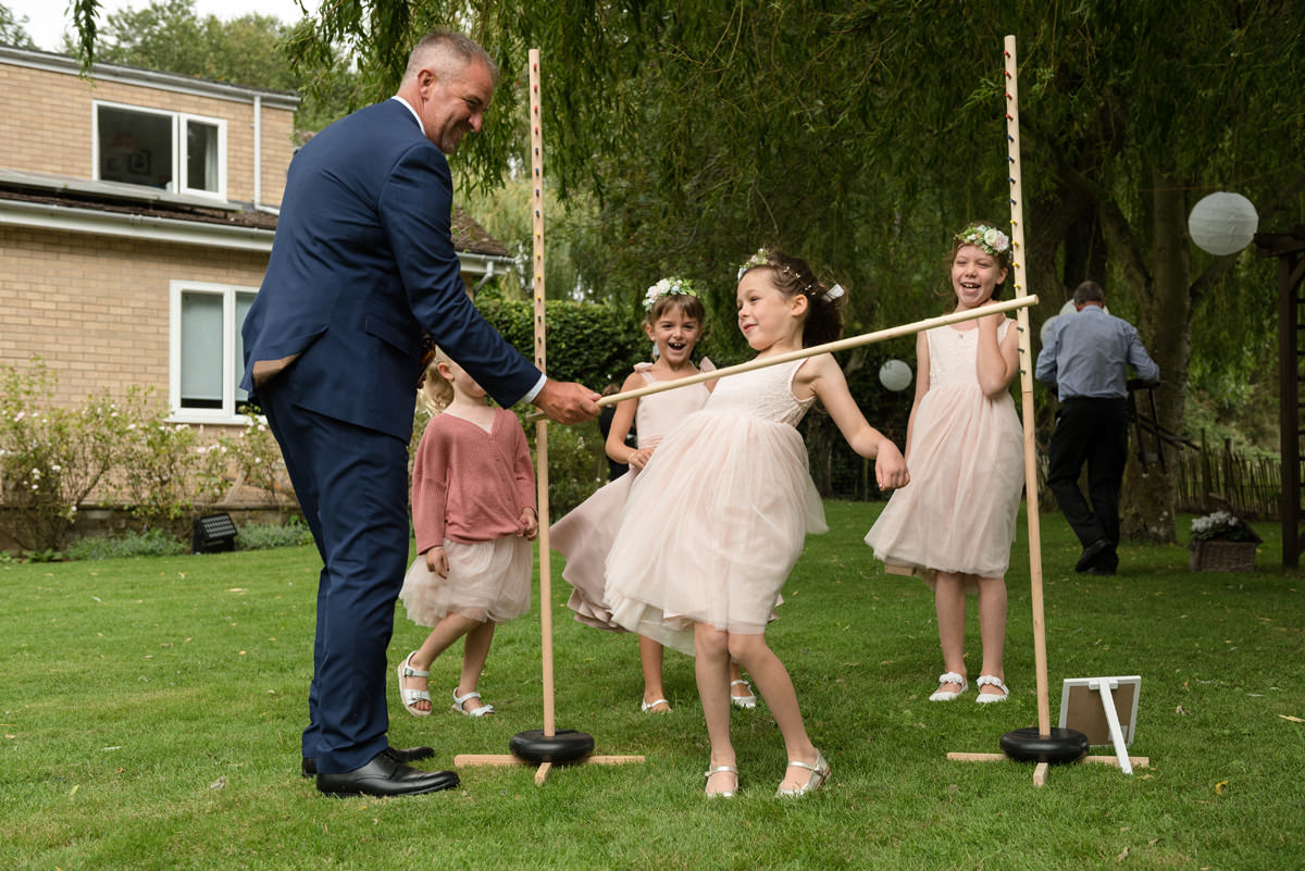 Children playing limbo at a wedding reception