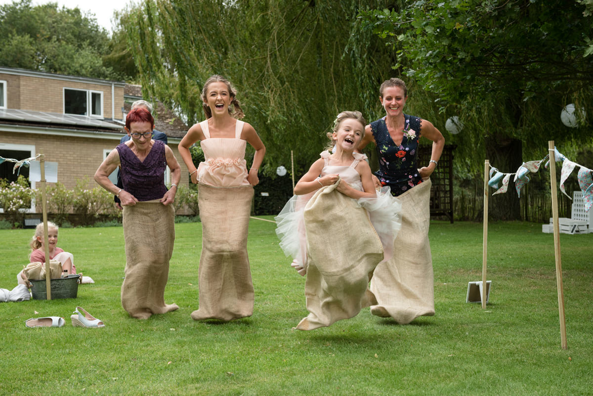 Family enjoying a sack race at a garden party wedding reception