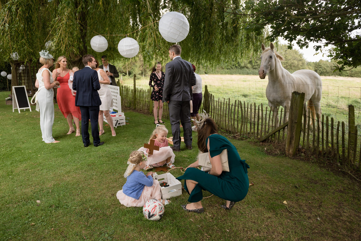 White horse looking on as guests play garden games at a wedding