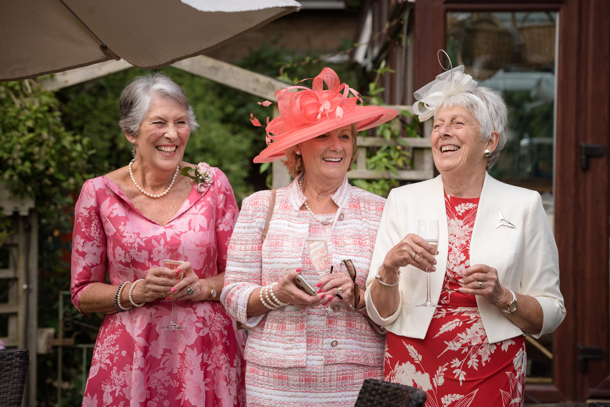 Three ladies in a row laughing at a wedding