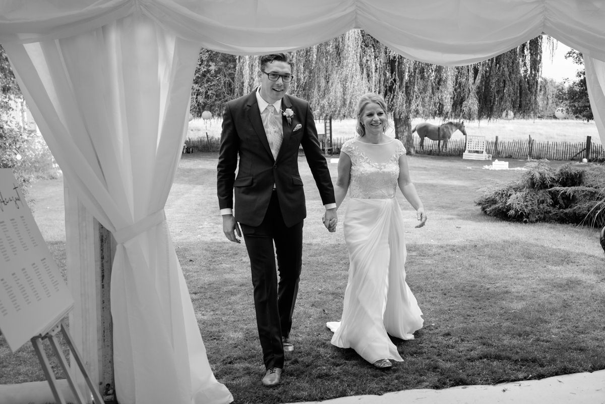 Bride and groom entering marquee for wedding breakfast