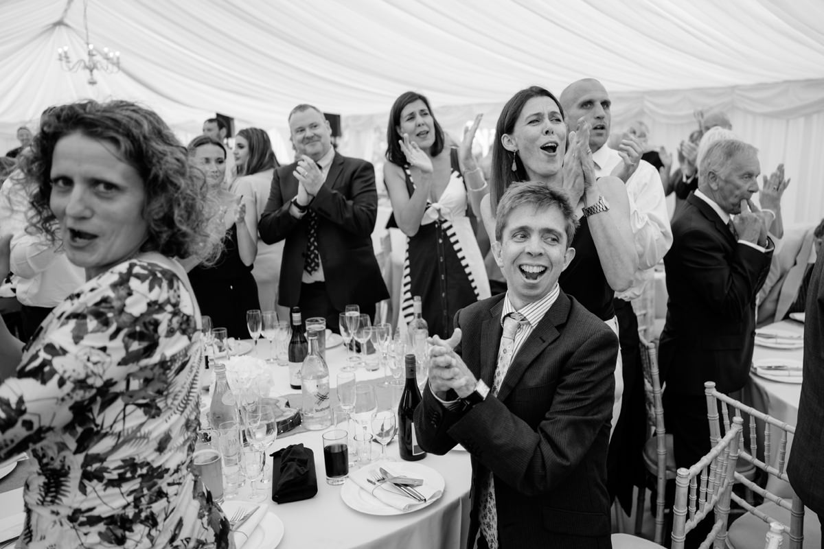 Wedding guests cheering couple into the marquee for dinner