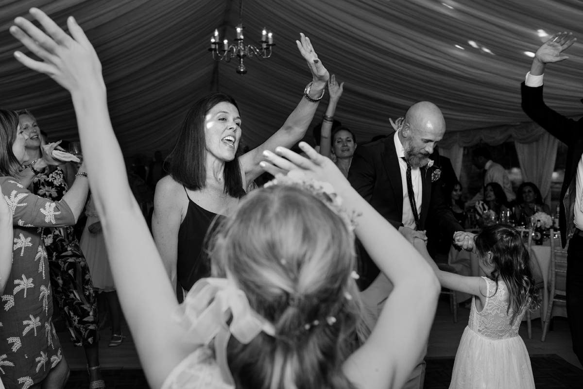 Wedding guests dancing with hands in the air