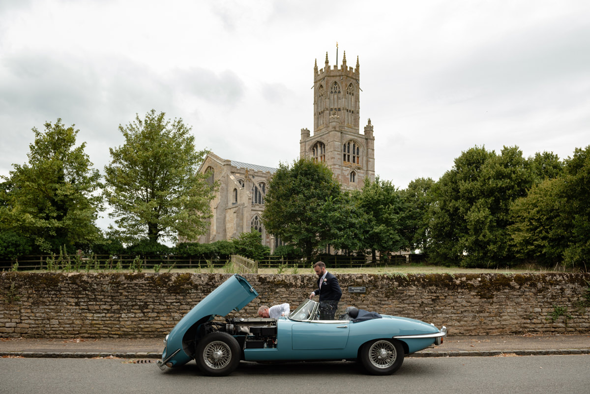 Broken down vintage wedding car in front of Fotheringhay church