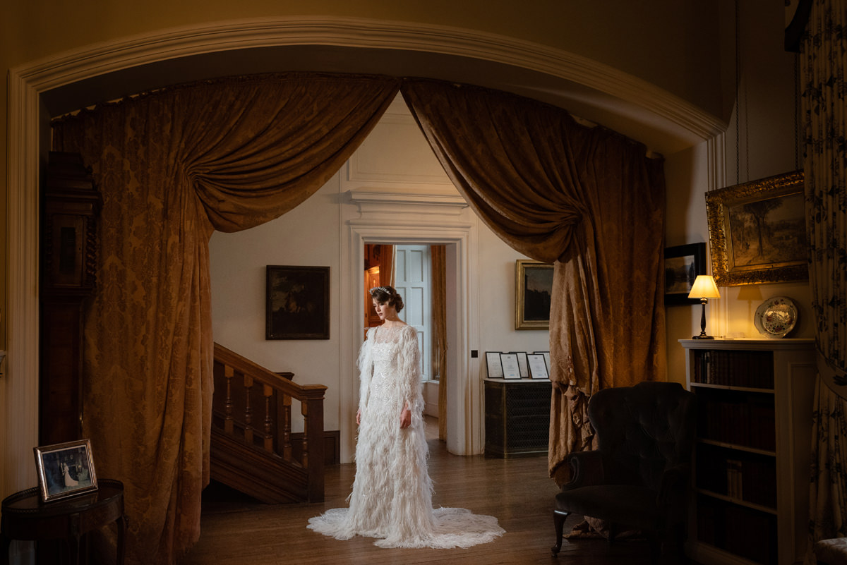 Model wearing an Eliza Jane Howell feather cape & dress at Holdenby House