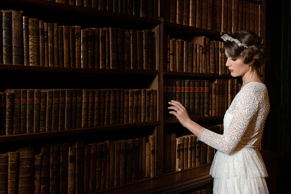 Model posing in the library at Holdenby House