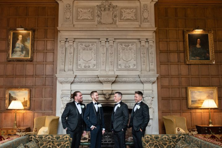 Groomsmen in front of the fireplace in the Great Hall at Rushton Hall