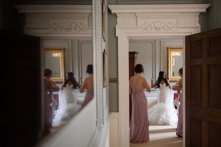 Reflection in TV of bride putting her perfume on at Rushton Hall