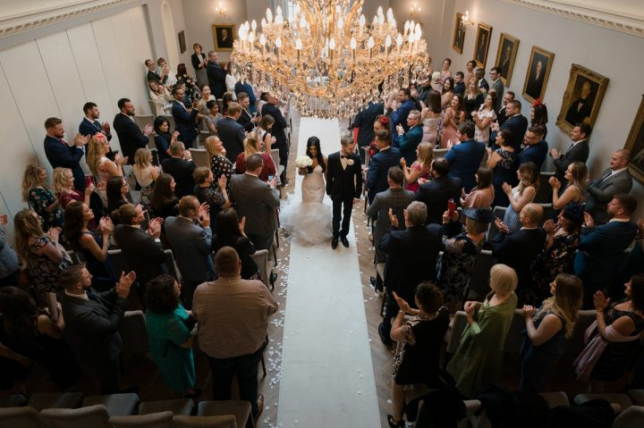 Bride and groom walking down the aisle at Rushton Hall