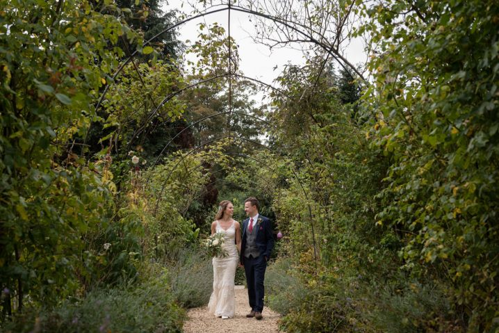 Bride and groom walking through an arch at The William Cecil