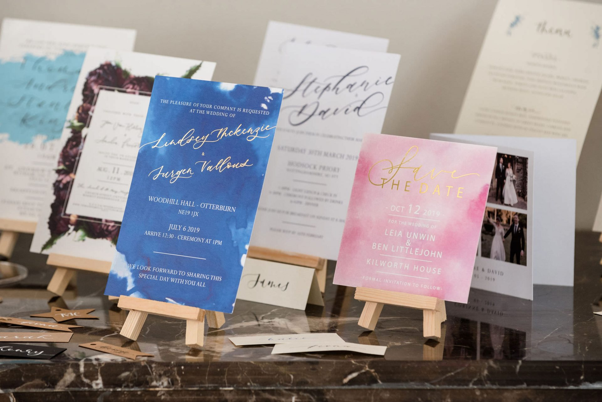 A display of invitations on mini wood easels