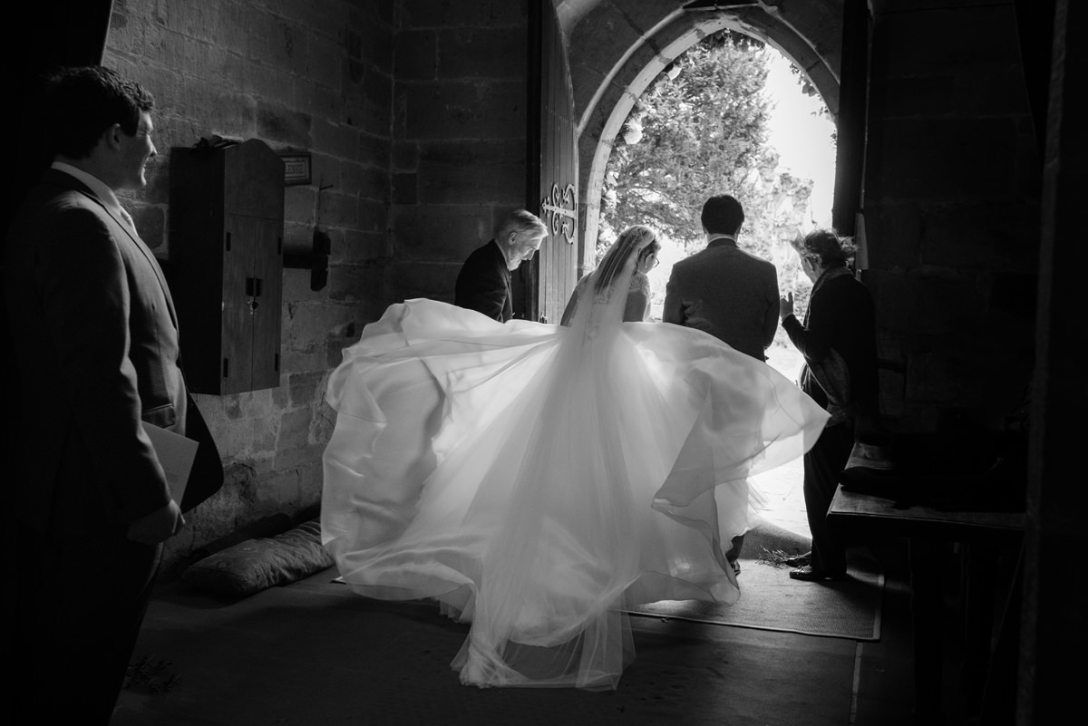 Bride and groom leaving Grandborough church on a windy day