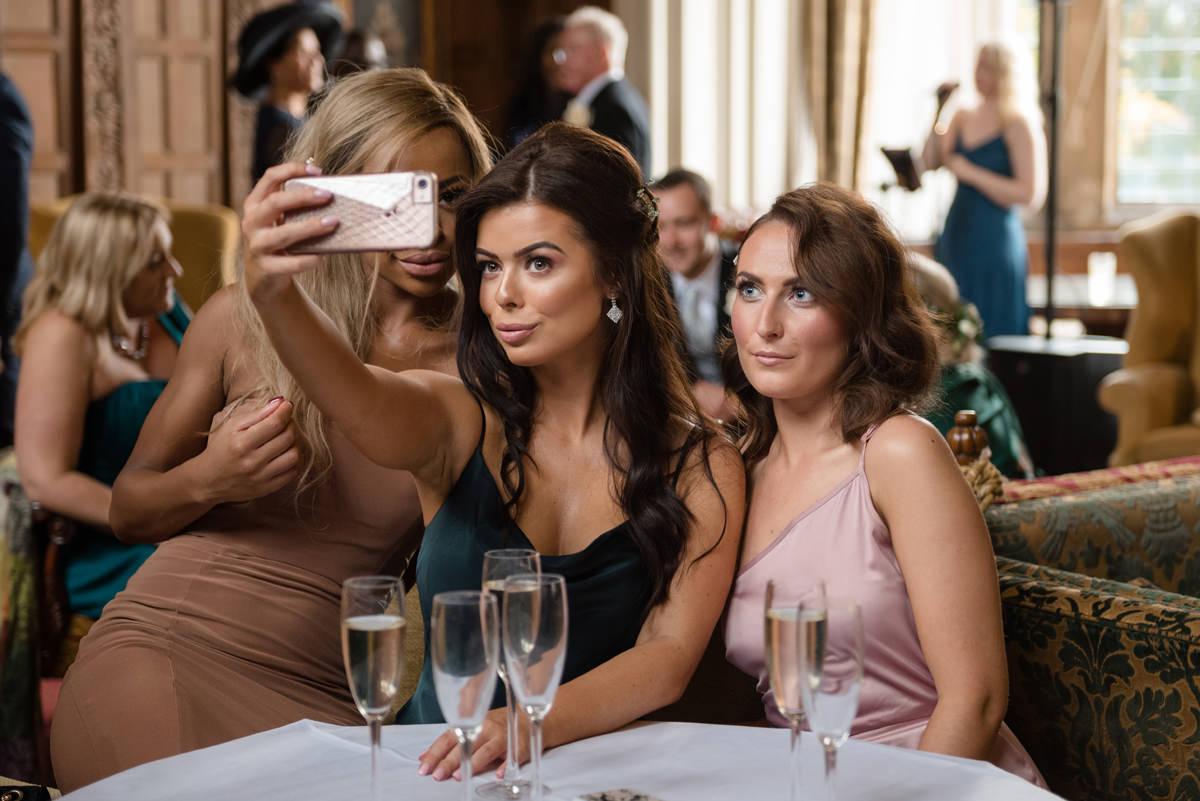 Group of three glam ladies taking a selfie