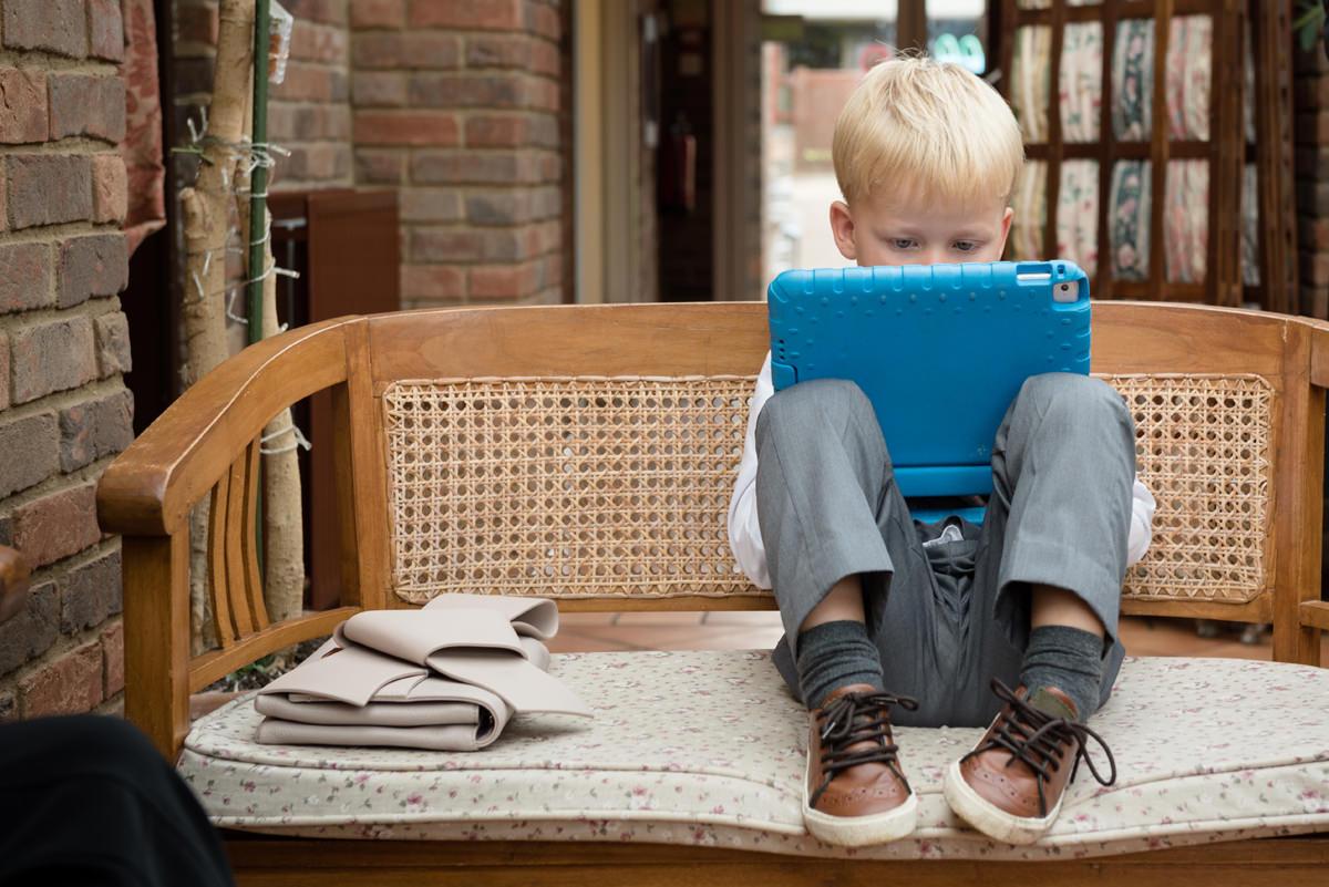 Little boy on a tablet at a wedding