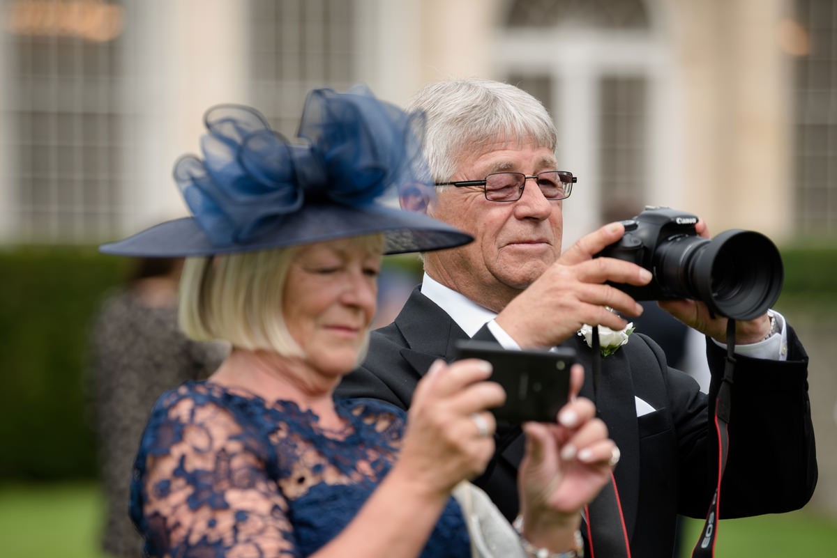 Two people taking photos, one with a DSLR and one with a phone